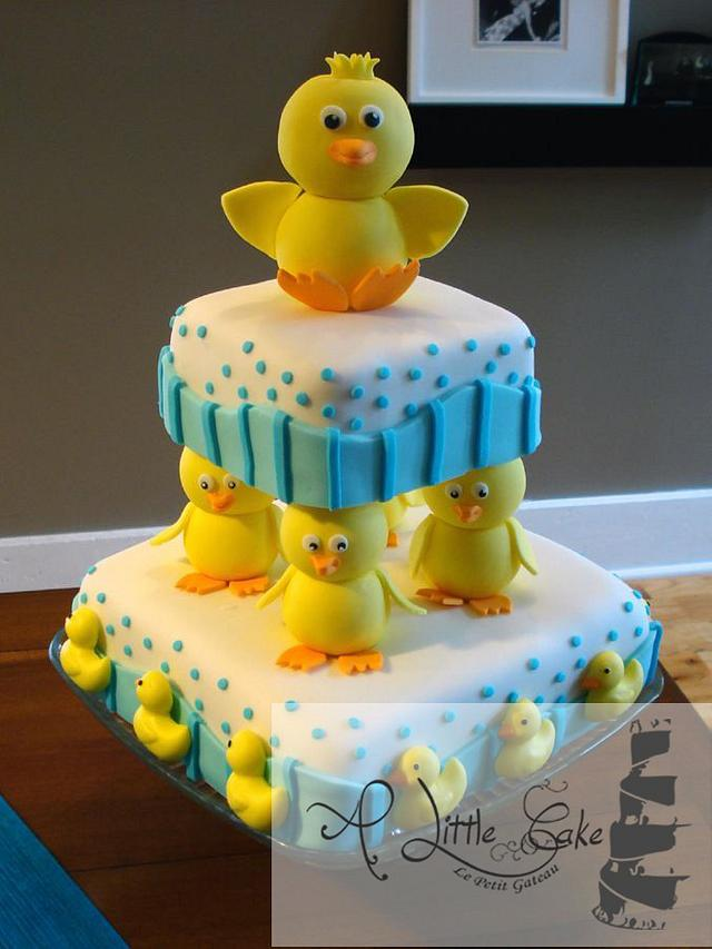 yellow ducks made of fondant on a blue and white two tier square cakes - Baby shower cake Tutorials