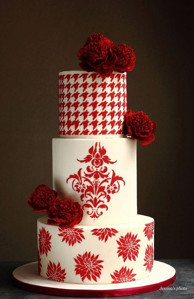 A 3 tier red and white theme cake with red flowers and chequered red and white stenciling done on it - Valentine's Day Cake Tutorials