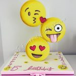 A gravity cake with tongue out and kissing emojo on it