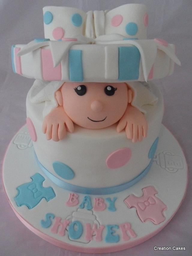 a simple white round cake with blue and pink polka dots and a fondant baby