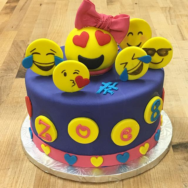 Purple fondant cake topped with fondant smiling faces all around