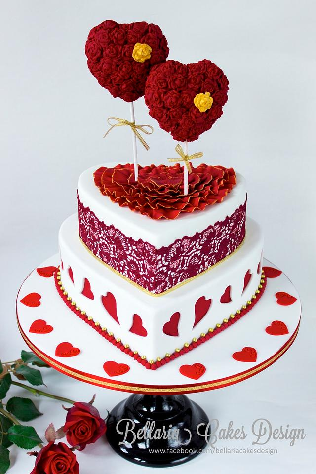 A 2 tier cake with red heart shaped cake lollipops on it