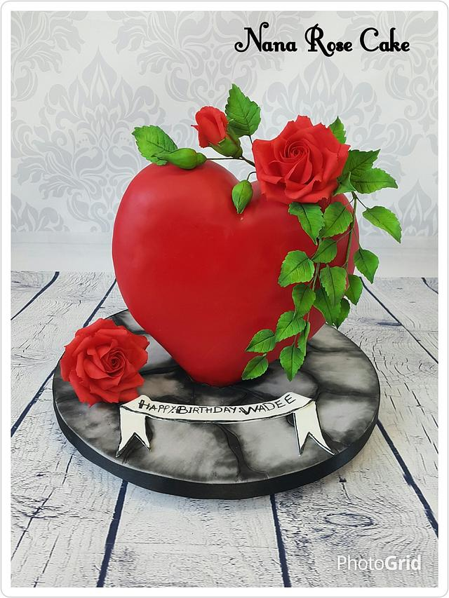 A standing heart shaped cake with red roses and green leaves on it