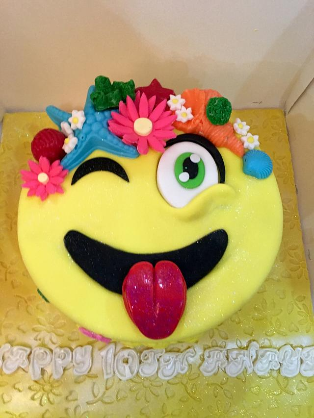 Tongue out emoji cake with a crown on flowers on the emoji
