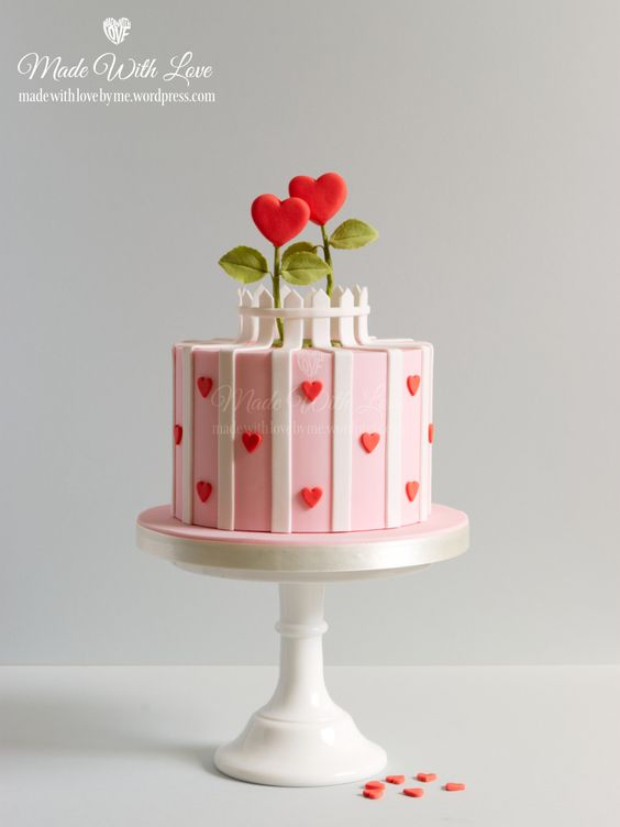 a pink heart cake with heart shaped flowers on it