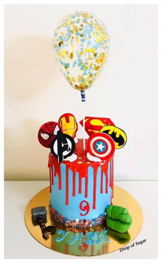 A simple drip cake with sprinkles at the base of the cake and fondant superhero symbols on top of it with a big baloon on it - Superhero Cake Tutorials