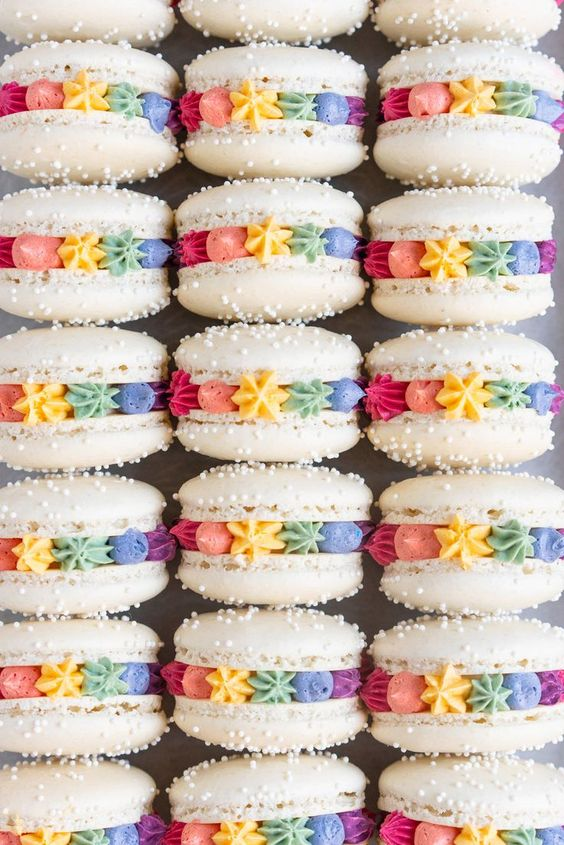 white macarons with sprinkles and colorful frosting with piped ster shapes