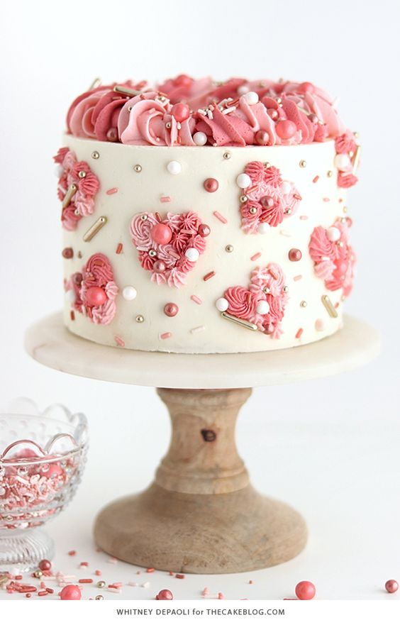white cake with hearts made of pink shades of buttercream and topped with sprinkles - Valentines Day Fun Tutorials