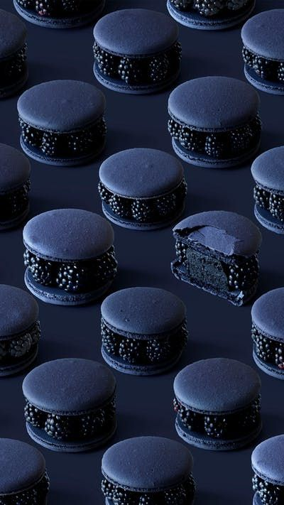 blackberry macarons in dark blue photograply