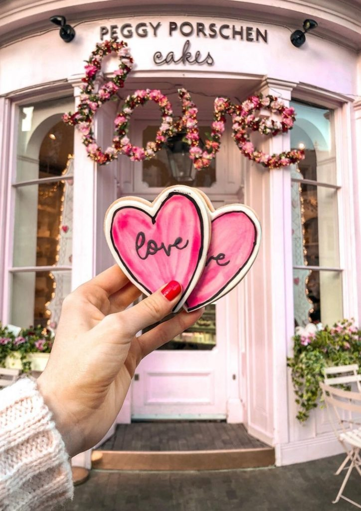 heart shaped cookie painted with light pink and love written with black