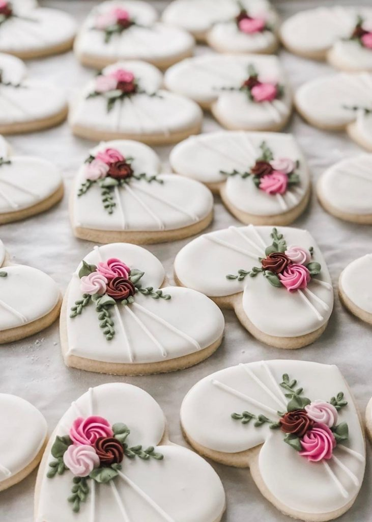 white cookie royal icing work with flowers and leaves
