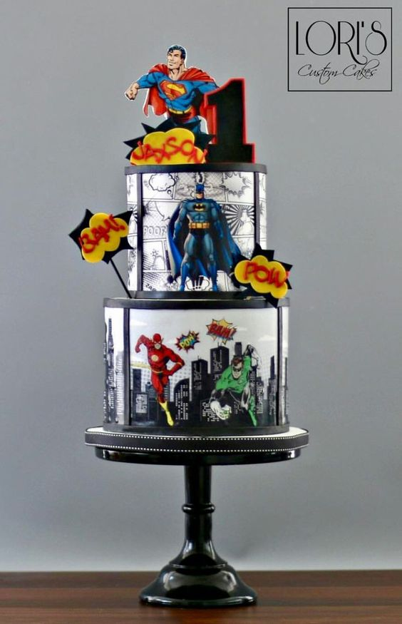a three tier superman cake with edible print superman and batman character put on it