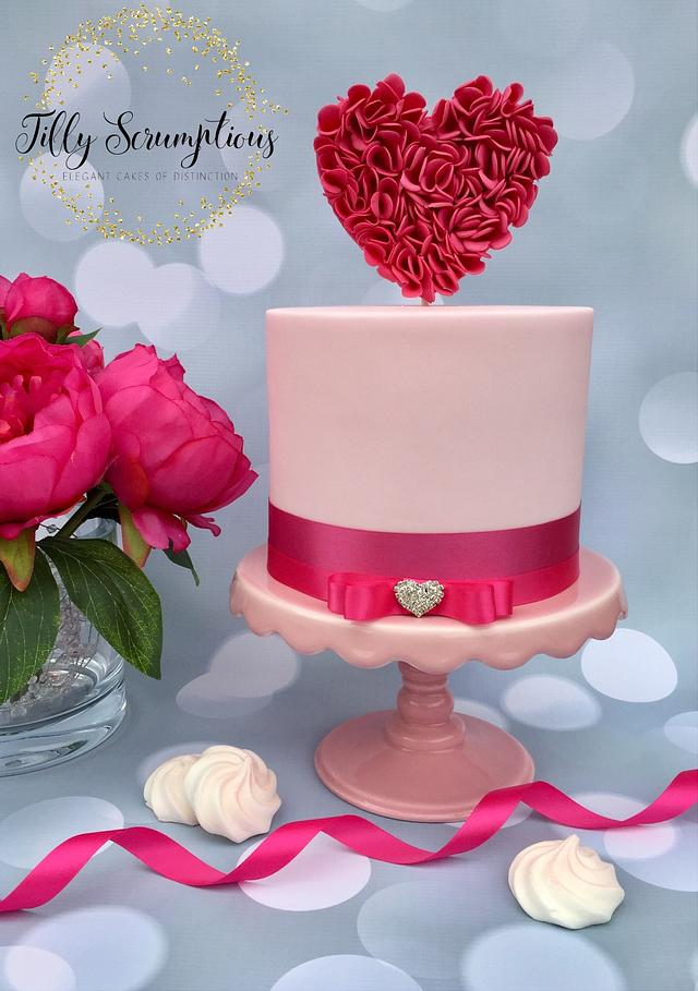 a pink fondant cake with a standing sugar heart made on frills in dark pink