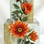 easy orange buttercream flowers on a two tier square cake with buttercream leaves