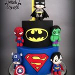 two tier cake with superman and batman theme and figurines made of sugar