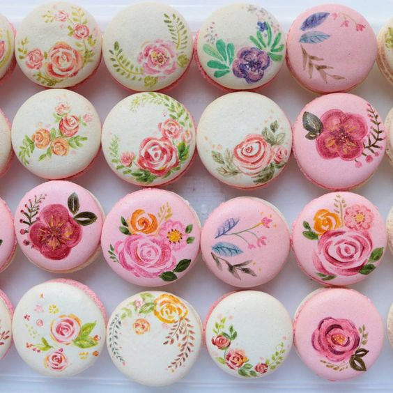 pink and white macarons with floral painting on it
