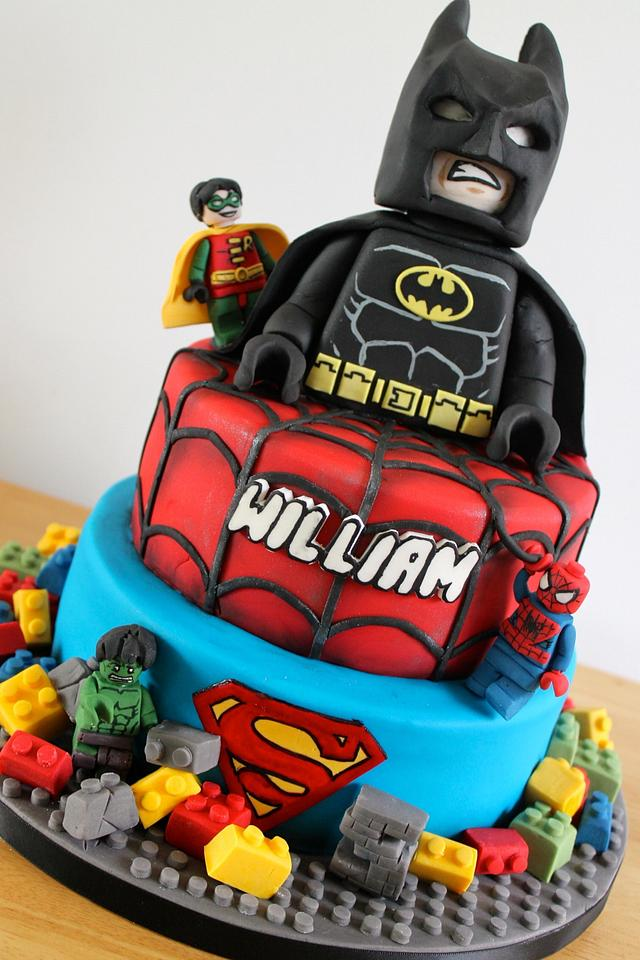 A batman figure made of fondant on top of a blue and red tier cake