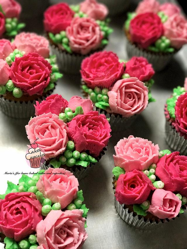 pink flowers and green leaves frosted on cake