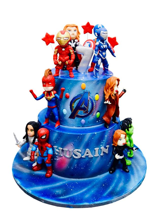 a blue and red avengers theme cake with characters on it