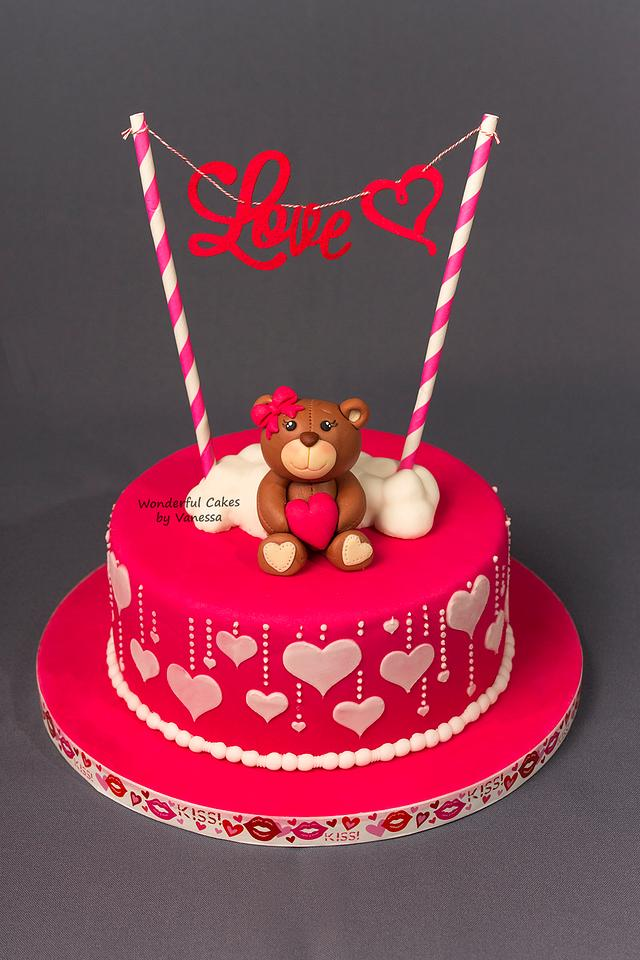 sugar teddy on a red cake with love written on it