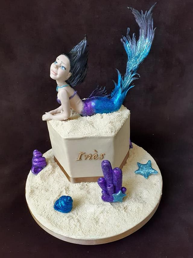 a mermaid with shimmer in blue and purple shiny tail on a cake