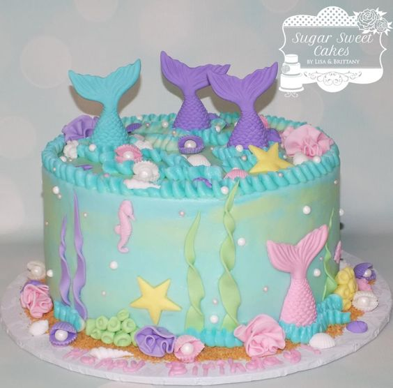 green frosted cake with tails of fishes popping out