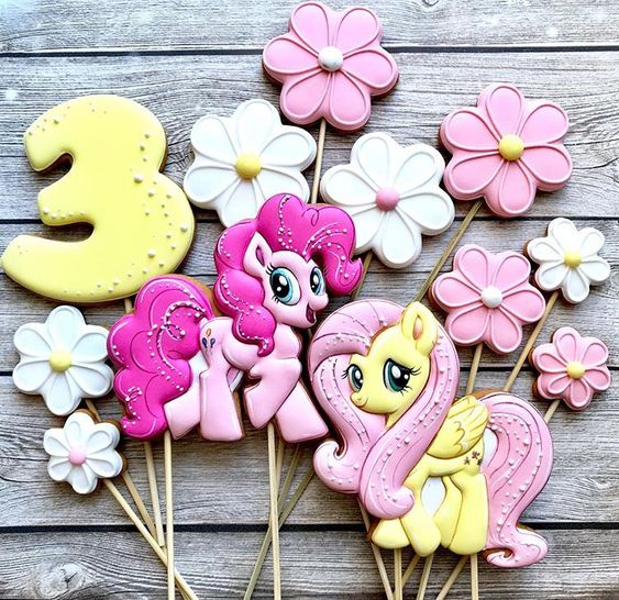 coloful yellow or pink unicorn cookie with flower cookies and number 3 cookies