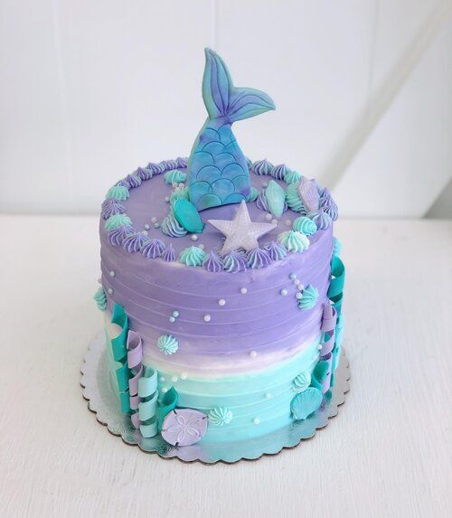 blue and purple cake with a mermaid tail popping of fondant