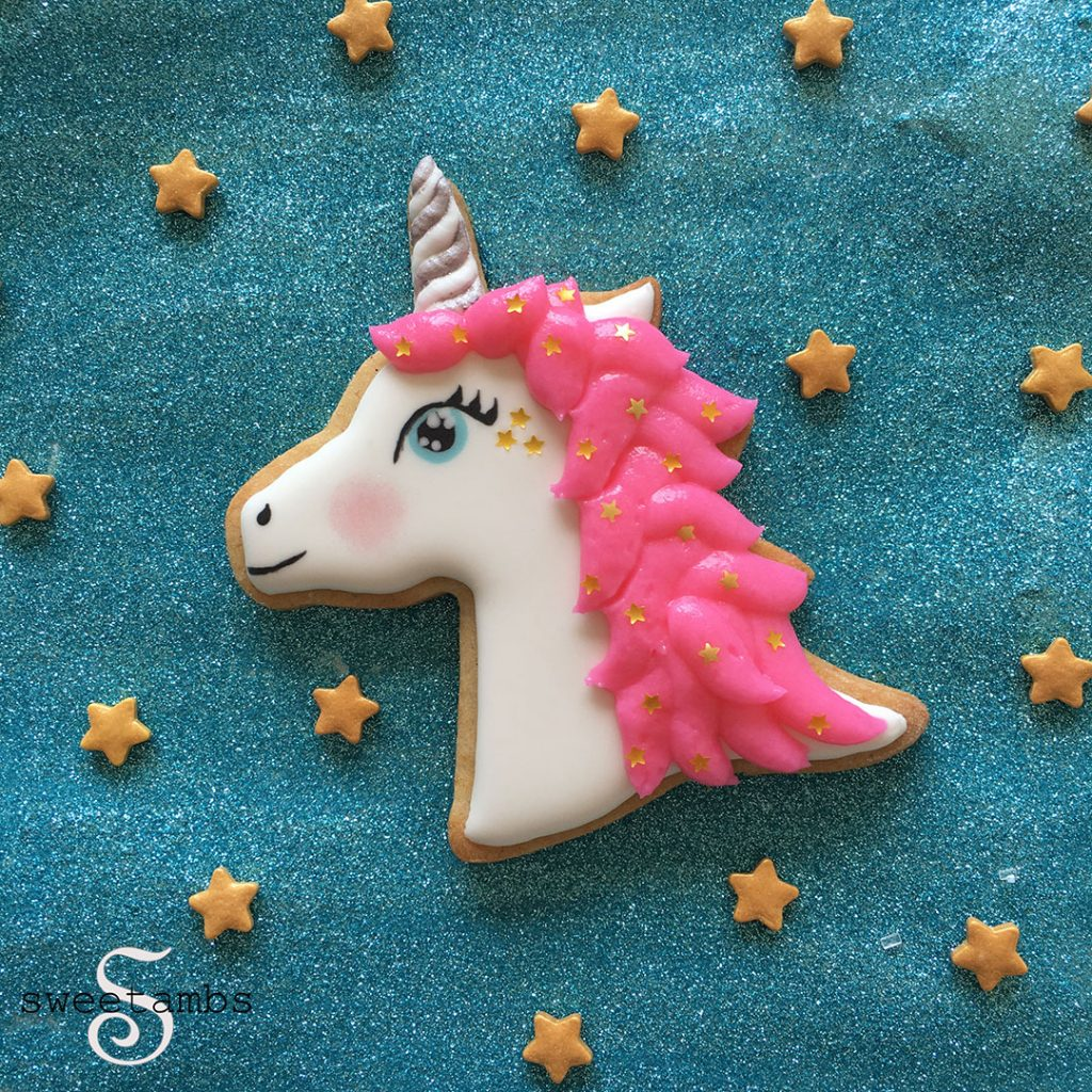 white horse shape biscuit with pink royal icing work with a unicorn horn