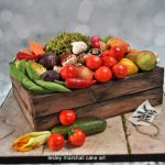 a wooden box effect cake with fondant carved tomatoes, garlic, green peas and more