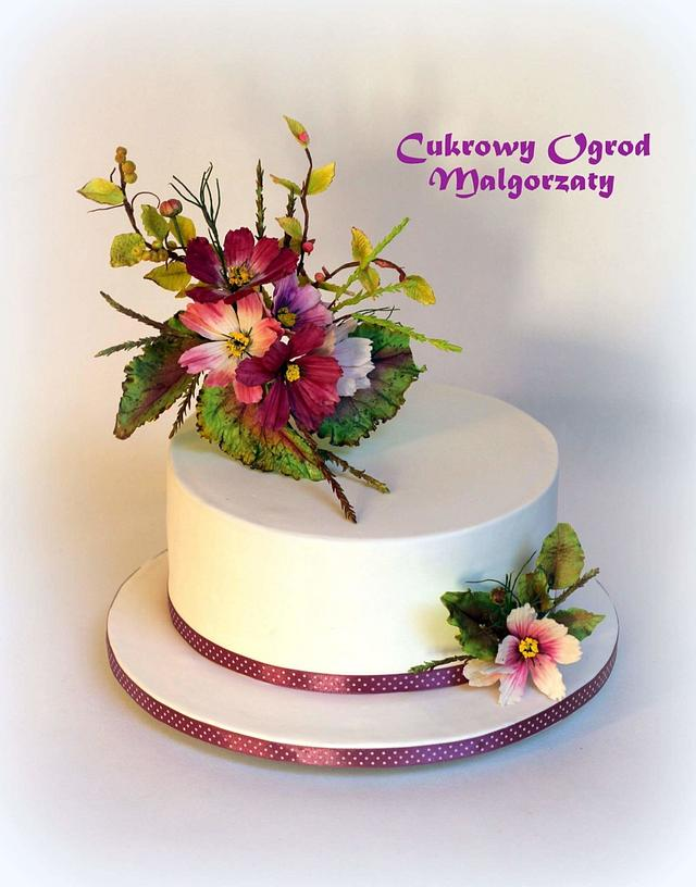 a white cake with flowers and leaves made of fondant