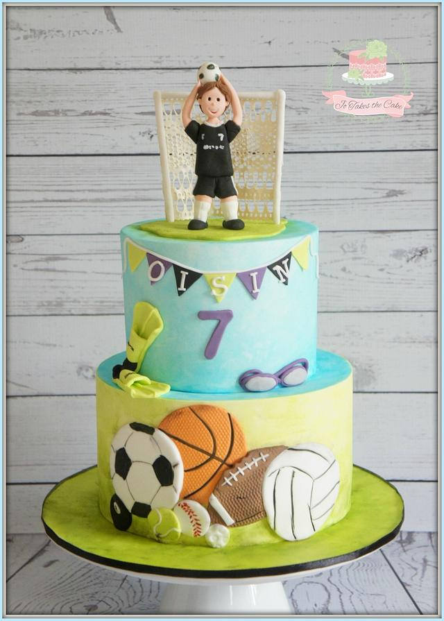 a two tier football fondant creation with sugar firgurine player and toppers