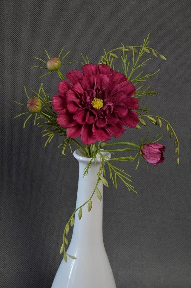 a red handmade cosmos flower out of gumpaste