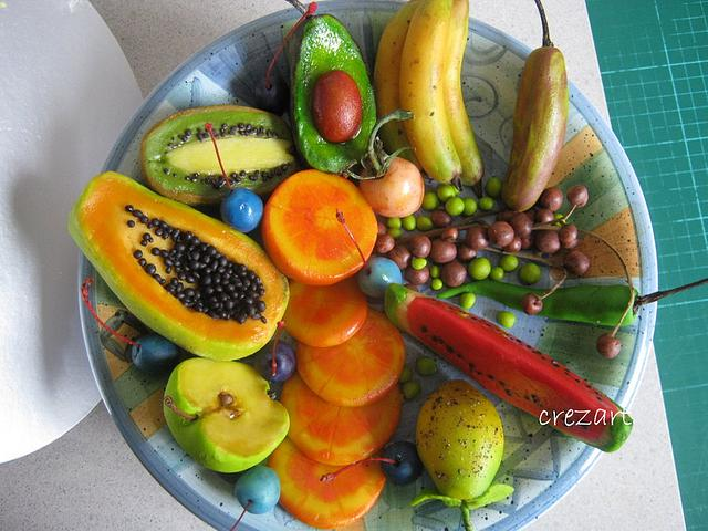 a plate full of caved veggies and fruits made of marzipan