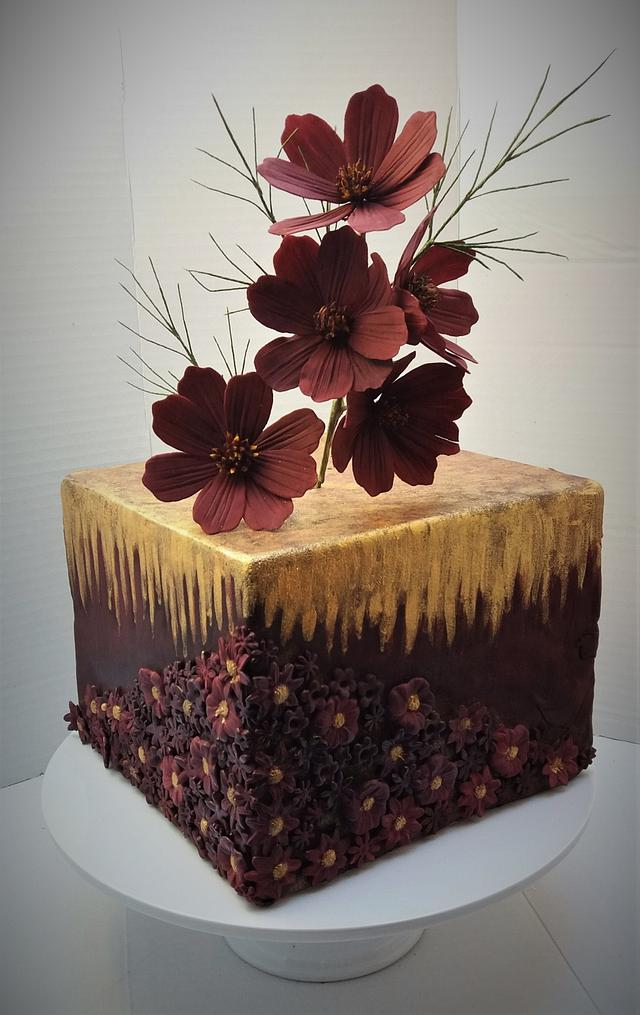 a square brown and gold cake with brown cosmos made of gumpaste on it