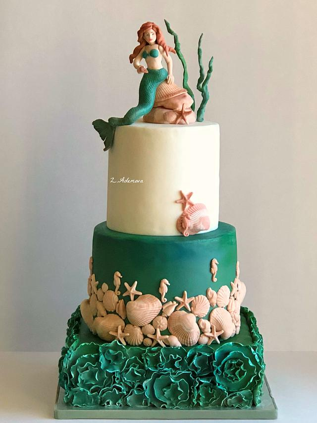 a green and off white cake with a mermaid sitting on the rock - Mermaid Cake Tutorials