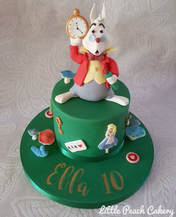 green fondant cake with a mousse character holding a clock made of fondant