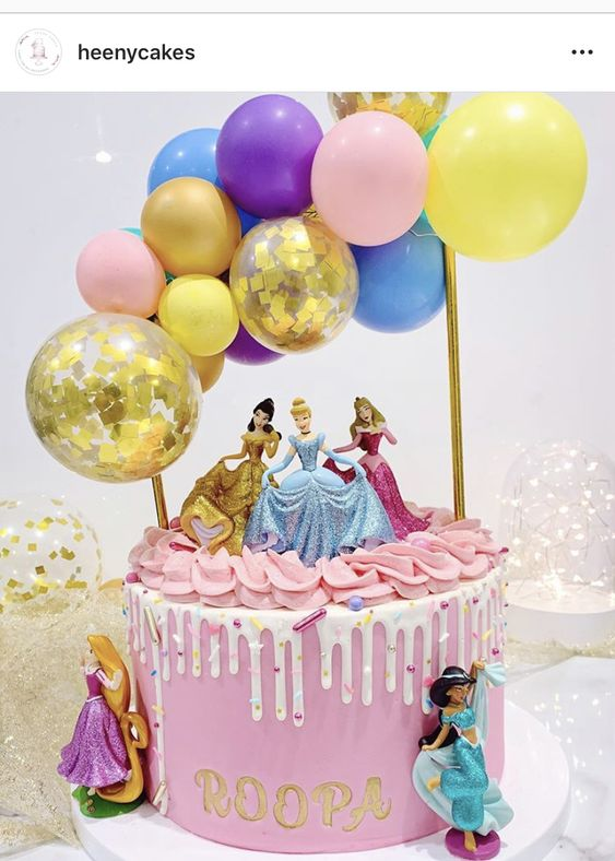 a princess theme with balloons on a pink cake with white drip effect on it