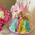 a disney theme cake with a pink crown and ruffle colorful dresses of sugar and a pink rose