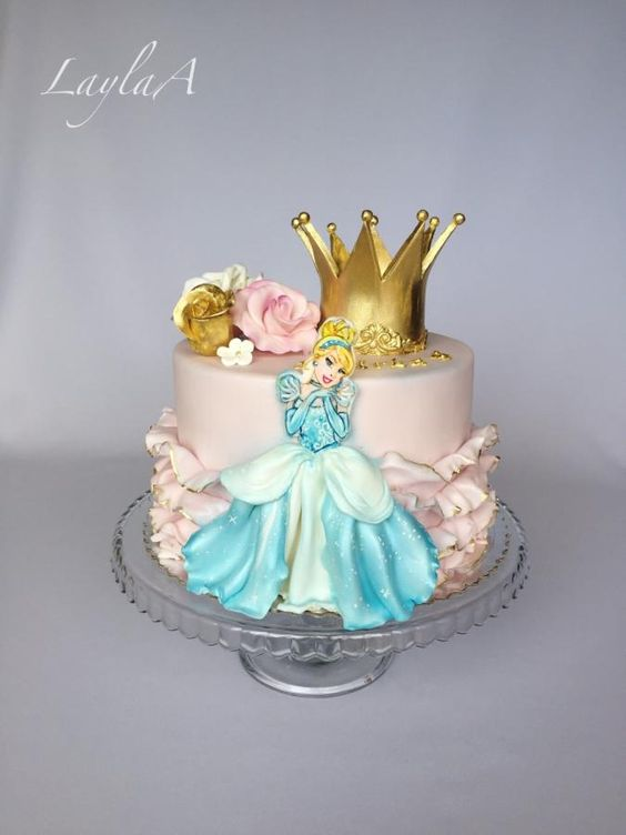 a golden crown made of sugar with a disney princess on it and sugar roses