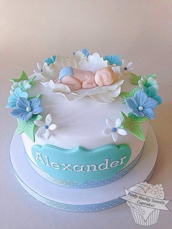 edible sugar baby with sugar flowers in blue and green and the child's name written on it