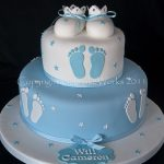 blue and white fondant theme cake with fondant booties and feet impression