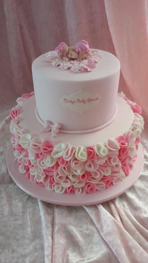 pink and white ruffle cake with a fondant baby on it made on sugar