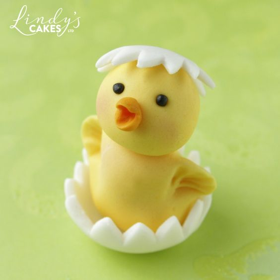 a fondant yellow chicken made of fondant in a white sugar egg shell