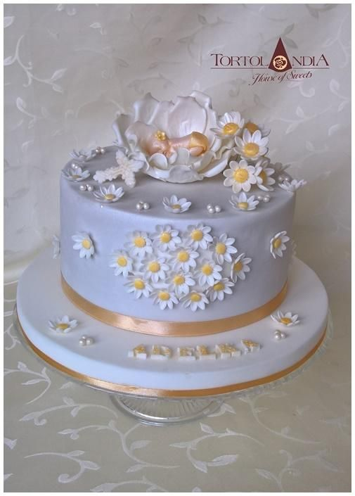 sugar sunflower on the cake with gold ribbon on the bottom and