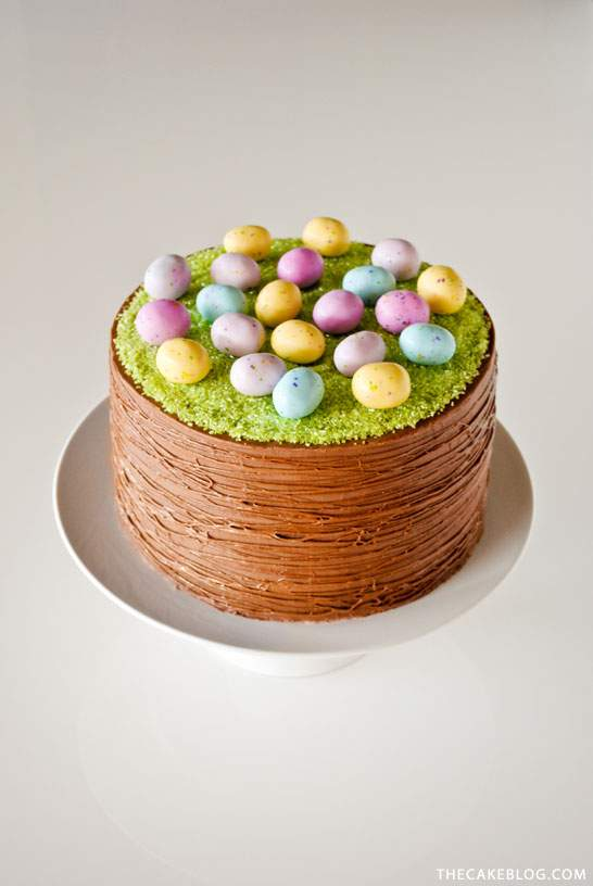 a chocolate cake with frosted grass effect frosting and colorful chocolate eggs placed on it