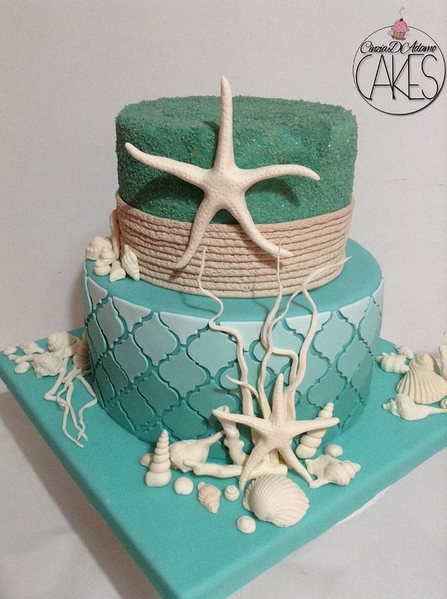 a green and blue fondant theme with stars and shells made of white fondant