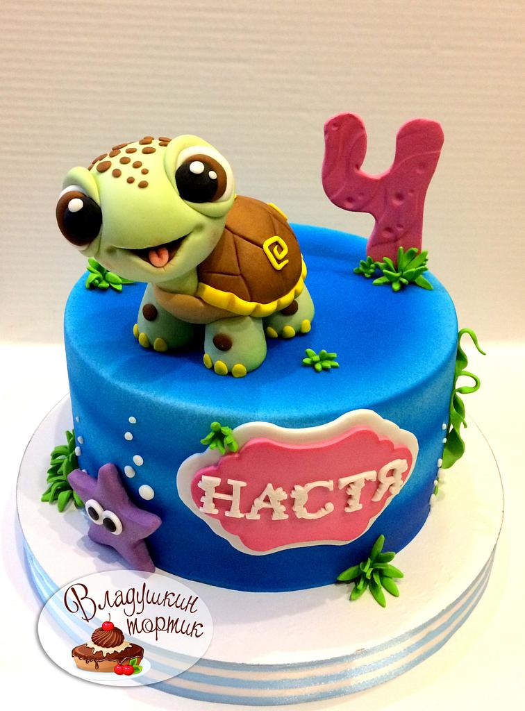 a playful sugar turtle made of fondant on a blue aqua theme cake - Sea creature cake tutorials