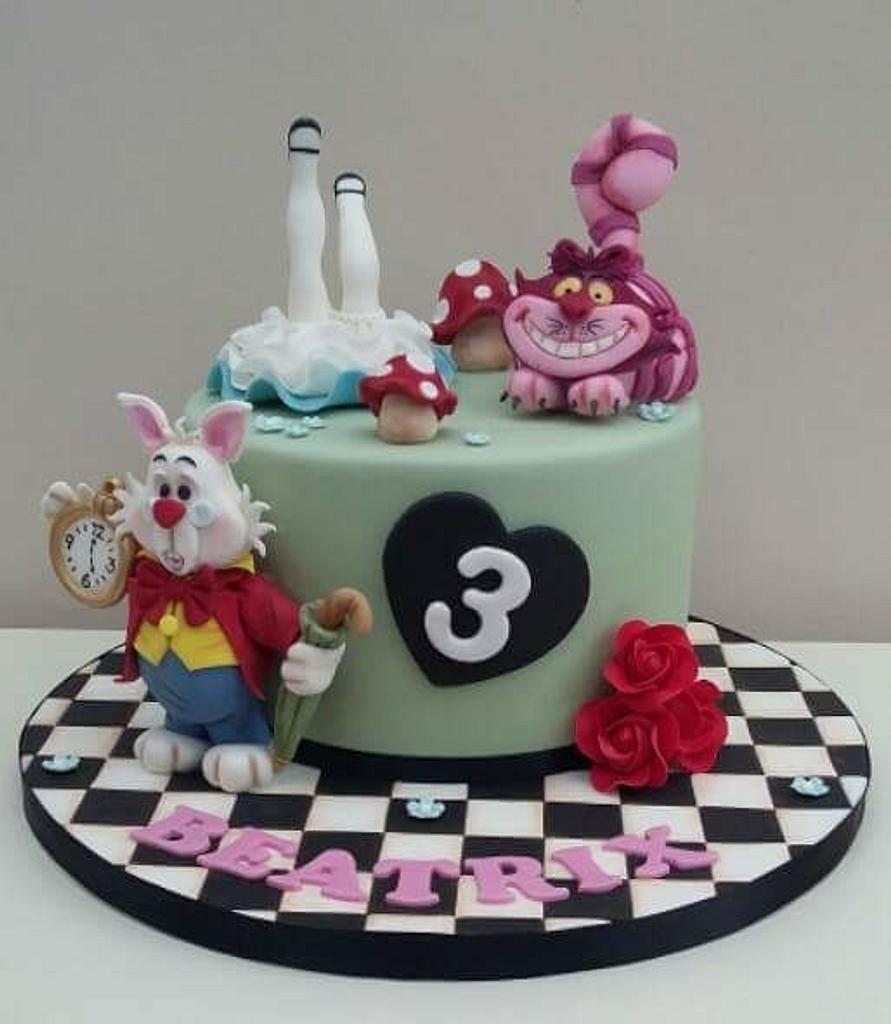 checquered black and white cake board with alice in wonderland figurines