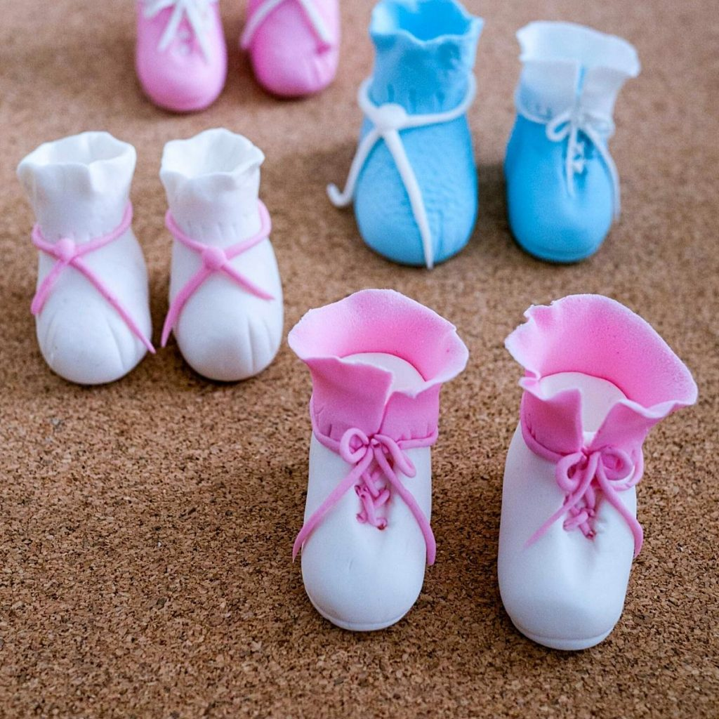 Two pairs of baby bootie and baby shoes on a table.